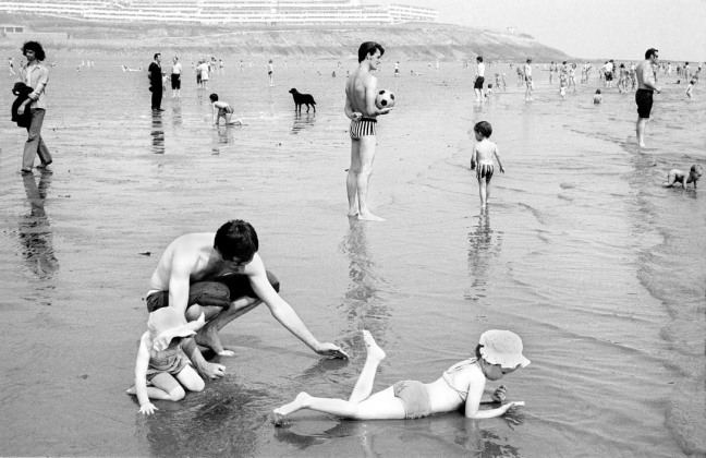 David Hurn - G.B. WALES. Barry Island. General. A father with his children relax on the beach at Barry Island, South Wales. The picture is during the 'miners' week' the holiday period of the miners of South Wales. It is probable that most of the people on the beach are miners on their holiday. Due to the closing of the pits this cultural happening no longer takes place. 1973 - © David Hurn